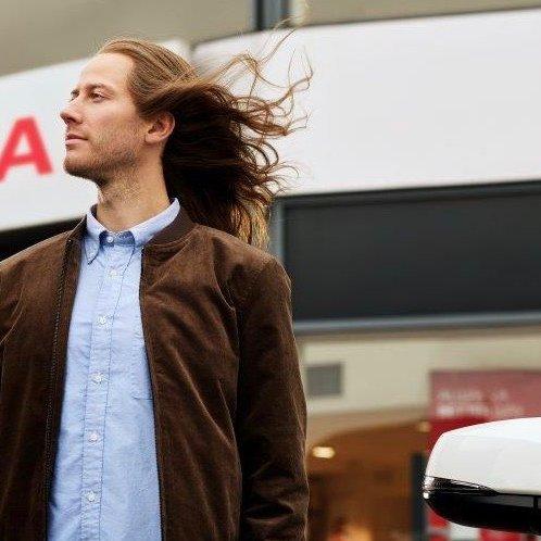 Toyota Relax Jüngling mit wehendem Haar vor Toyota Händler